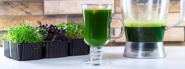 Microgreensap op de keukentafel. microgroenten in een blender. maak thuis een microgroene smoothie. gezond en biologisch eten
