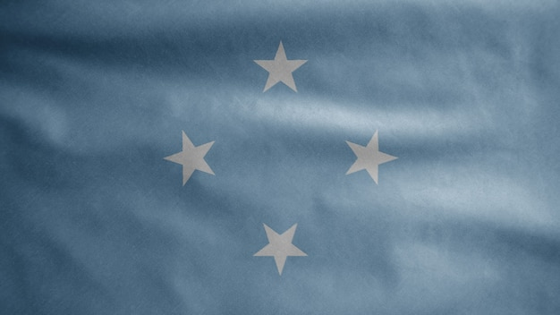 Micronesische vlag zwaaien op de wind. micronesië banner waait gladde zijde. doek stof textuur vlag achtergrond.