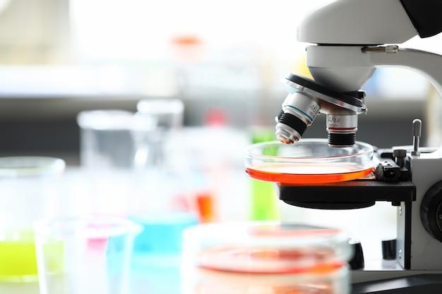 Microscoop die zich in het laboratorium van de schoolchemie onder flessen bevindt