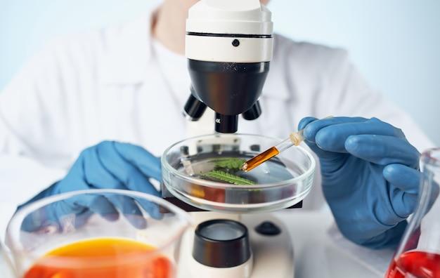 Microscoop op tafel en vrouwelijke laboratoriumassistent in blauwe handschoenenvloeistof in een kolf. hoge kwaliteit foto