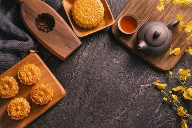 Mid-autumn festival traditioneel voedselconcept - mooie maancake op zwarte leisteentafel met thee, gebakvorm, bloem, bovenaanzicht, plat leggen, kopieerruimte