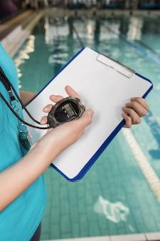 Mid sectie van coach met een stopwatch en klembord bij zwembad