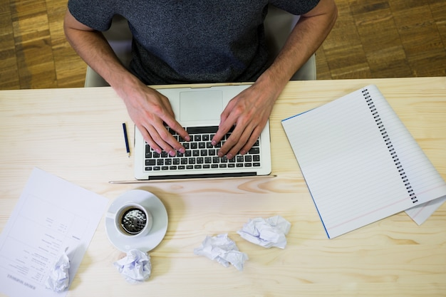 Mid-sectie van de mannelijke business executive met behulp van laptop