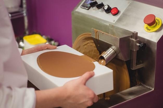 Mid sectie van de werknemer vullen mal met gesmolten chocolade