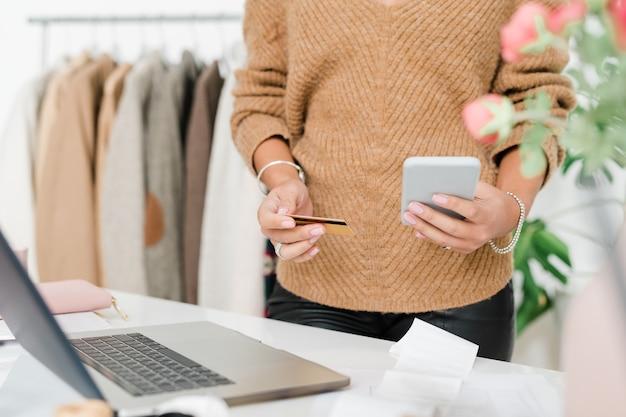 Mid-sectie van jonge elegante vrouw in beige pullover scrollen in smartphone terwijl contactloze betaling gaat doen