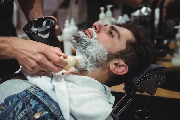 Mid sectie van kapper crème op de baard van de klant toe te passen