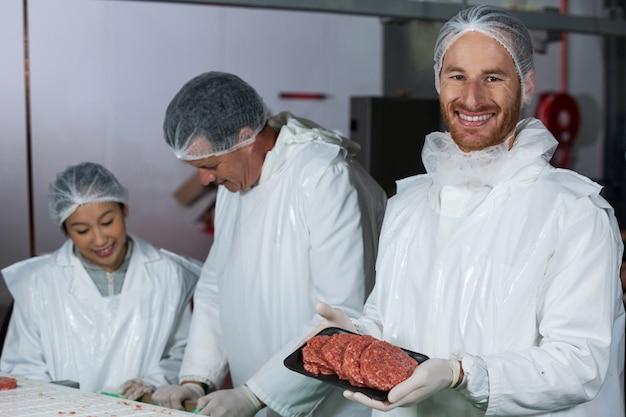 Mid sectie van slager met rauw vlees pasteitjes gerangschikt in lade