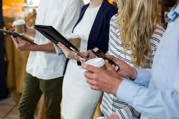 Mid-sectie van vrienden met behulp van digitale tablet en mobiele telefoon