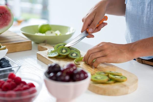 Mid-sectie van vrouw snijden fruit op snijplank tegen witte achtergrond