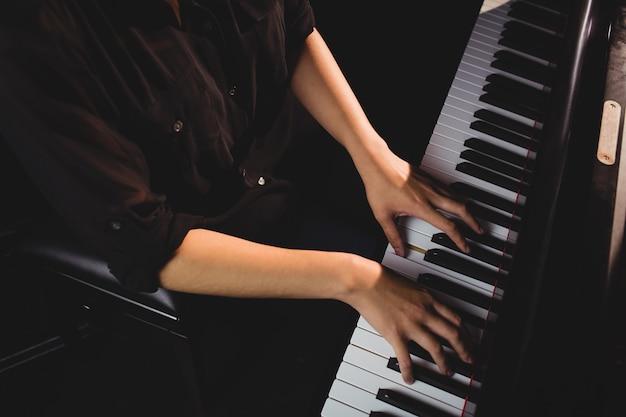 Mid-sectie van vrouwelijke student piano spelen