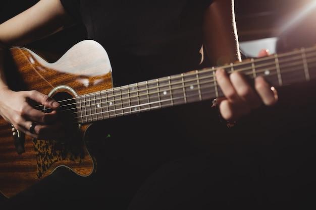 Mid-section vrouwelijke student gitaar spelen