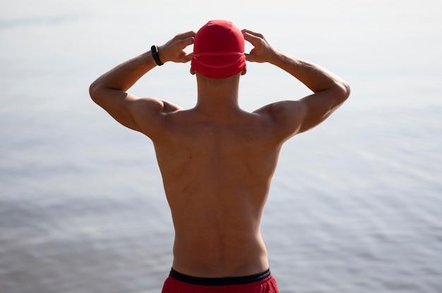 Mid shot atleet die zwembril bevestigt