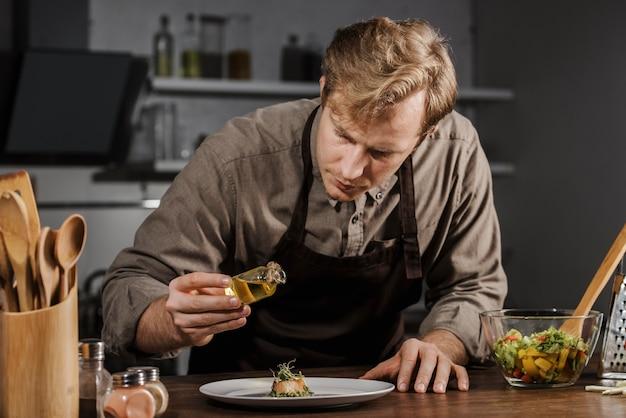 Mid-shot chef-kok schotel met olie