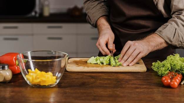 Mid shot chef-kok snijden salade