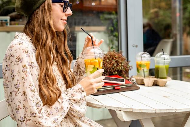 Mid shot jonge vrouw die vers drankje houdt en aan tafel zit