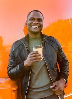 Mid shot man met koffie staan door voedsel vrachtwagen