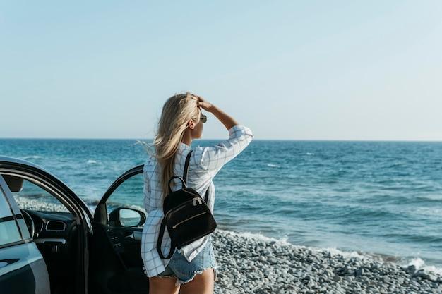 Mid shot meisje kijkt naar zee in de buurt van auto