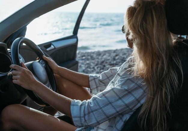 Mid shot meisje zit op de bestuurdersstoel in de buurt van de zee