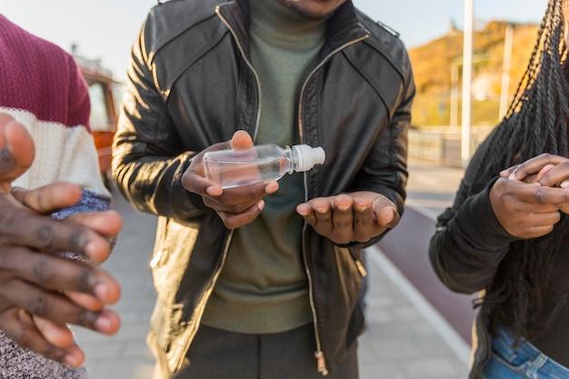 Mid-shot mensen die handen desinfecteren