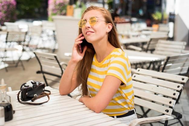 Mid shot vrouw aan tafel praten over de telefoon