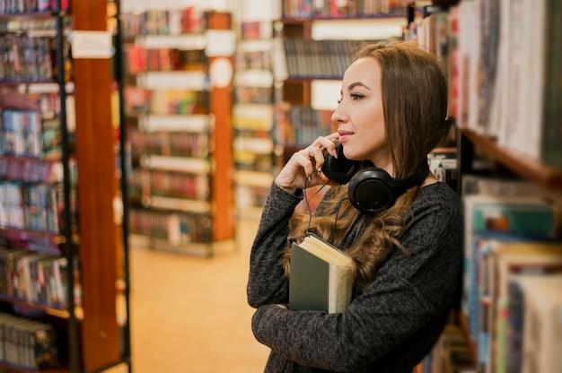 Mid shot vrouw draagt een koptelefoon om de nek knuffelen boek