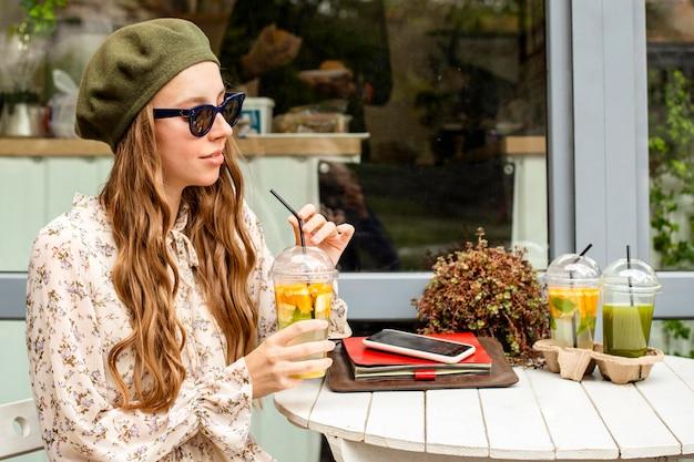 Mid shot vrouw met vers drankje en zittend aan tafel