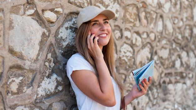 Mid shot vrouw praten over de telefoon in de buurt van de muur
