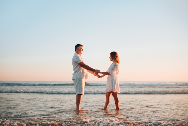 Mid volwassen paar hand in hand, witte jurken dragen op het strand tijdens een zonsondergang