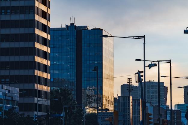 Middaglichten weerkaatst op de glazen gevel van verschillende kantoorgebouwen