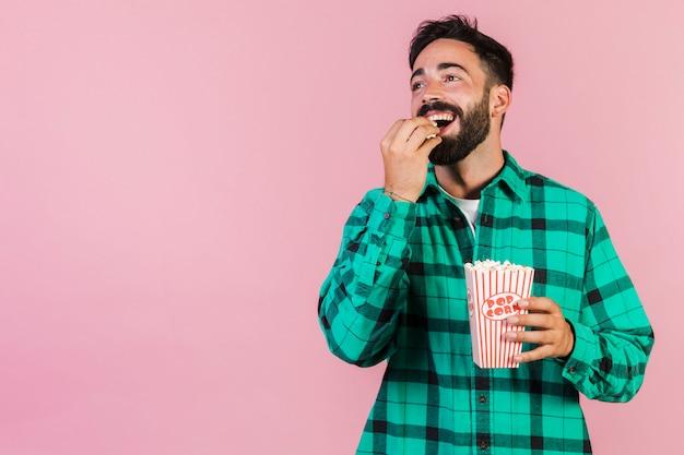 Middel geschoten gelukkige kerel die popcorn eet