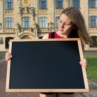 Middel geschoten middelbare schoolmeisje die bord kijken