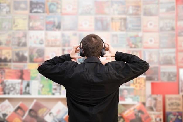 Middel geschotene achtermening van de jonge mens die aan muziek in opslag luisteren