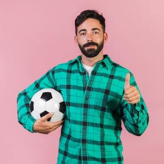 Middel geschotene kerel die een voetbalbal houdt
