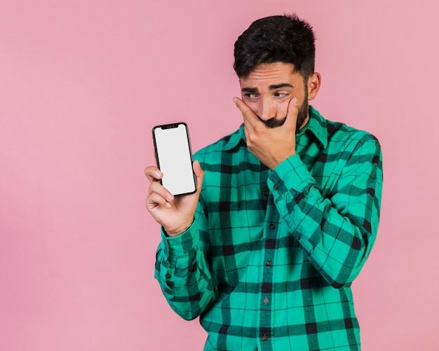 Middel geschotene kerel die zijn telefoon bekijkt