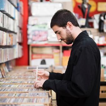 Middel geschotene zijaanzicht van de jonge mens die vinyls in opslag zoeken