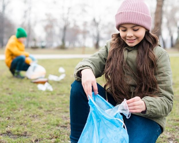 Middel schot van glimlachend meisje recycling