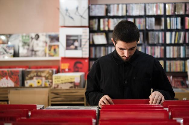 Middel van jonge mens wordt geschoten die vinyls in opslag zoeken die