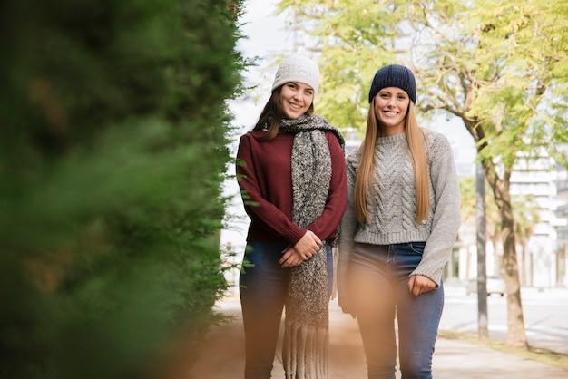 Middel van twee glimlachende vrouwen wordt geschoten die in het park lopen dat