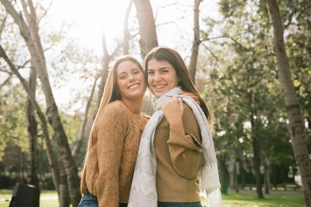 Middel van twee vrouwen wordt geschoten die in het park glimlachen dat