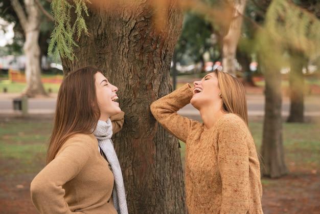 Middel van twee vrouwen wordt geschoten die in het park lachen dat