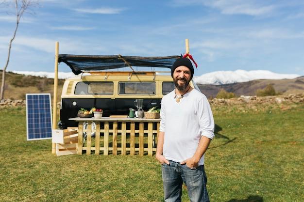 Middelbare bejaarde bebaarde man voor een bestelwagen van een foodtruck op een veld