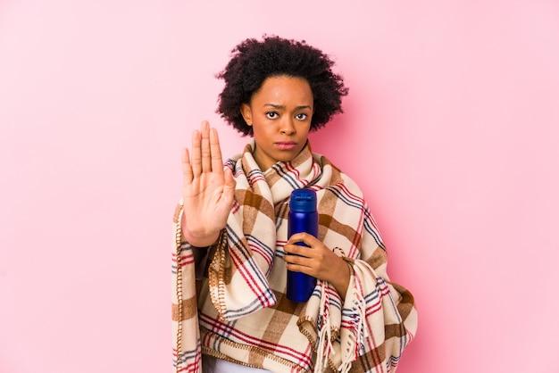 Middelbare leeftijd afro-amerikaanse vrouw in een camping staan met uitgestrekte hand met stopbord