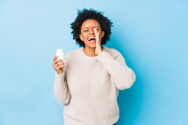Middelbare leeftijd afro-amerikaanse vrouw met een vitaminefles opgewonden schreeuwen