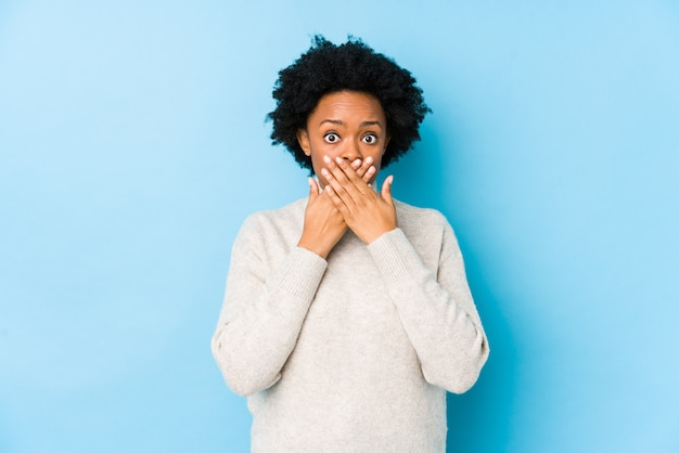 Middelbare leeftijd afro-amerikaanse vrouw tegen een blauwe geïsoleerde geschokt over mond met handen.