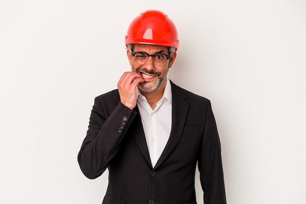 Middelbare leeftijd architect blanke man geïsoleerd op witte achtergrond vingernagels bijten, nerveus en erg angstig.