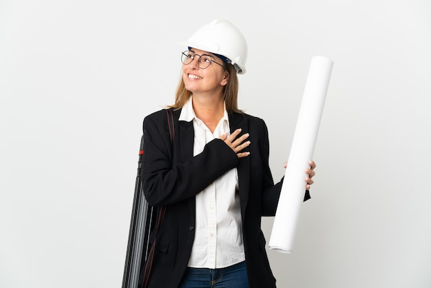 Middelbare leeftijd architect vrouw met helm en blauwdrukken houden over geïsoleerde achtergrond opzoeken tijdens het glimlachen