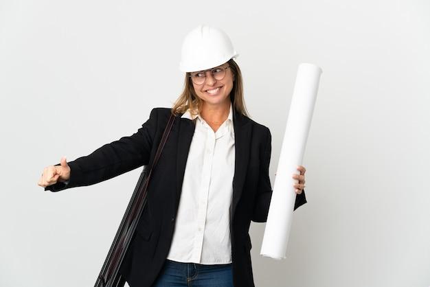 Middelbare leeftijd architect vrouw met helm en blauwdrukken houden over geïsoleerde muur met een duim omhoog gebaar