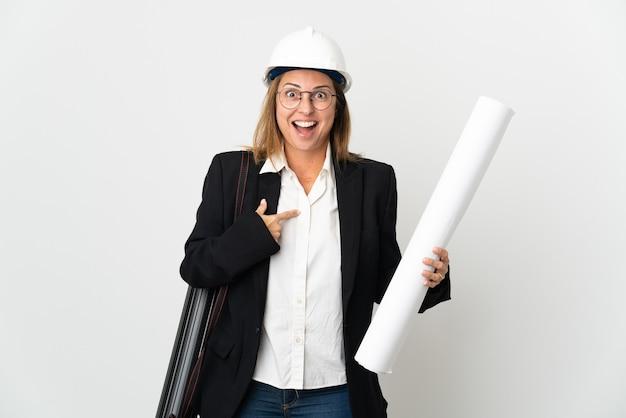Middelbare leeftijd architect vrouw met helm en blauwdrukken houden over geïsoleerde muur met verrassingsgelaatsuitdrukking
