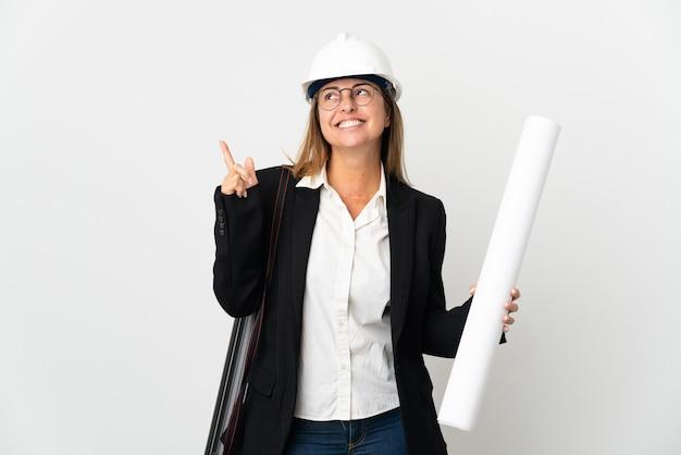 Middelbare leeftijd architect vrouw met helm en blauwdrukken te houden over geïsoleerde een geweldig idee te benadrukken