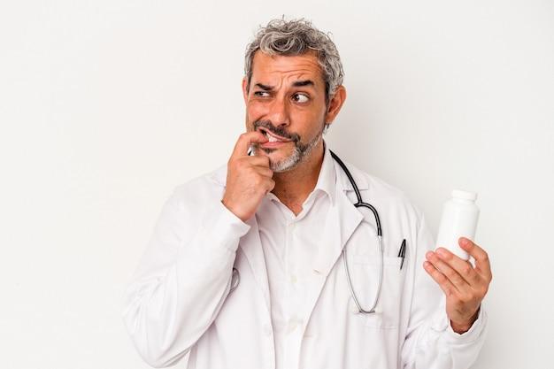 Middelbare leeftijd arts blanke man geïsoleerd op een witte achtergrond ontspannen denken over iets kijken naar een kopie ruimte.